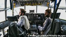 Taliban fighters sit in the cockpit of an Afghan Air Force aircraft at the airport in Kabul on August 31, 2021, after the US has pulled all its troops out of the country to end a brutal 20-year war -- one that started and ended with the hardline Islamist in power. (Photo by Wakil KOHSAR / AFP) (Photo by WAKIL KOHSAR/AFP via Getty Images)