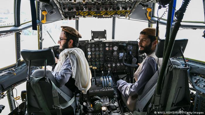 Talibanes sentados en la cabina de un avión de combate afgano.