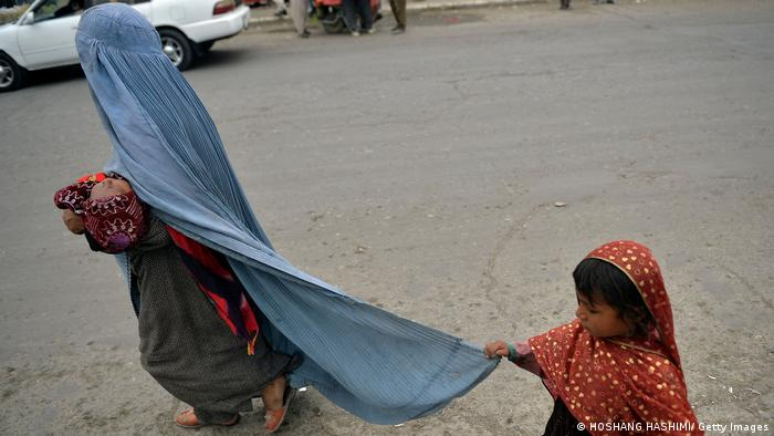 Una mujer con burka, con su hija y un bebé en brazos.
