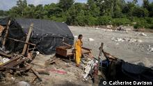 Pic 1 BU: Reena Bhalekar stands in the location where her house used to be before the floods swept it away. All that remains is her bed. ALT: Reena Bhalekar stands in the location where her house used to be in India.
