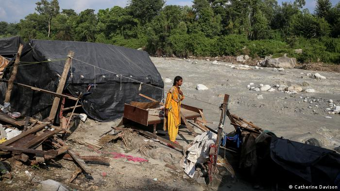 A woman stands next to her destroyed home