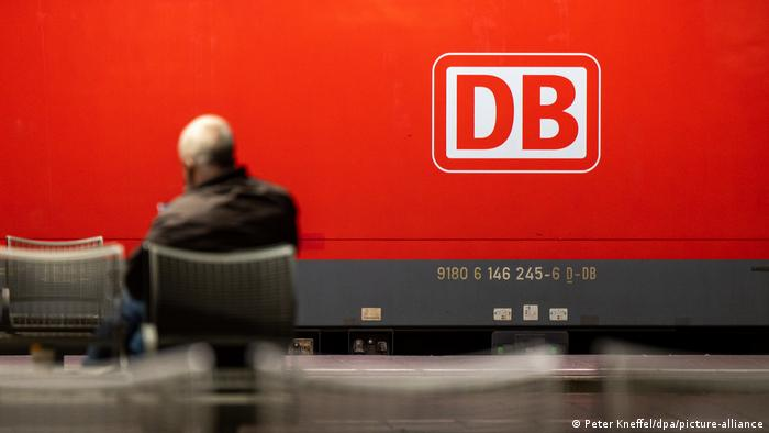 A man sits at a train station in Germany
