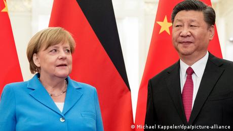 Angela Merkel and Xi Jinping stand in front of the alternating flags of their home nations