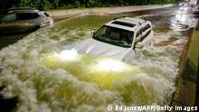 TOPSHOT - A motorist drives a car through a flooded expressway in Brooklyn, New York early on September 2, 2021, as flash flooding and record-breaking rainfall brought by the remnants of Storm Ida swept through the area. (Photo by Ed JONES / AFP) (Photo by ED JONES/AFP via Getty Images)
