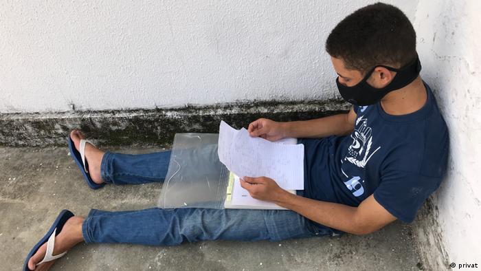 Vitório da Silva Ferreira sentado no chão lendo papéis