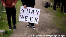 1. Mai Demo DEU, Deutschland, Germany, Berlin, 01.05.2021 Demonstranten mit Schild 4 Day Week 4-tage-Woche zum 1. Mai auf der Demonstration von internationalen Gewerkschaften, linken Initiativen und des Gewerkschaftsverband DGB zum 01. Mai 2021 und dem Tag der Arbeit fuer einen Fairen Lohn, Solidaritaet und gerechte Arbeitsbedingungen in Zeiten von Corona unter dem Motto Nicht auf unserem Ruecken - Gewerkschaften und Lohnabhängige in die Offensive in Berlin. en: Protest with sign 4 Day Week 1. Mai, Out on May Day, at a Ralley of left wing unions and the union German Confederation of Trade Unions, DGB, in Berlin, Germany. Demonstrators participate at a May Day protest in the tradition of the International Workers Day, which was established