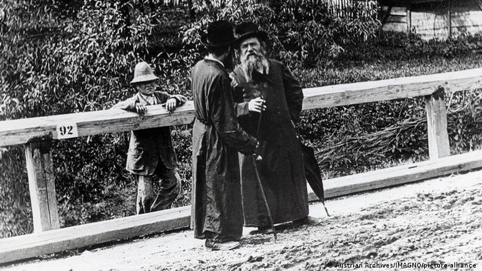Black and white photo of three men on a wooden bridge, 1900