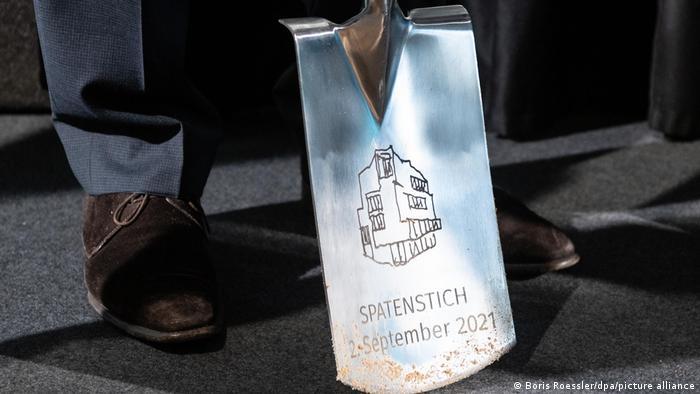 Glänzendes Blatt eines Spaten mit Gravur Spatenstich 2. September 2021 und Skizze des zu errichtenden Neubaus der Jüdischen Akademie in Frankfurt