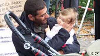 Der Palästinenser Firas Maraghy hält sein Baby im Arm und streichelt ihm den Kopf vor der israelischen Botschaft in Berlin (Foto: DW)
