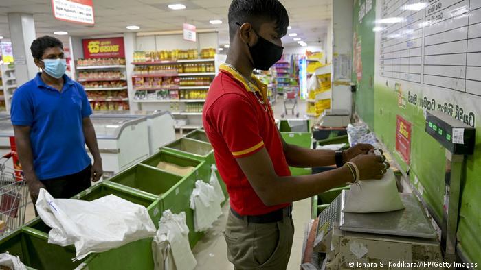 A supermarket worker weighs food