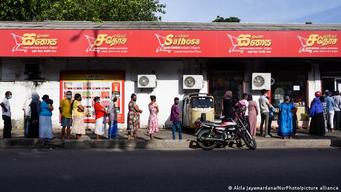 People wait in a queue outside a supermarket to buy essential foods in Colombo, Sri Lanka