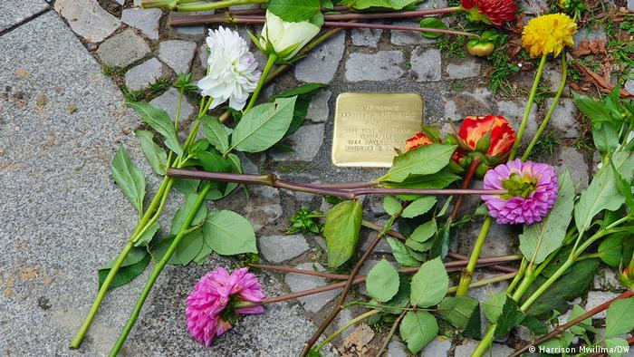 A Stolpersteine with fresh flowers commemorating the fate of Martha Ndumbe.