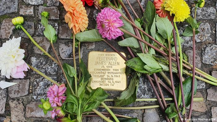 A Stolpersteine with fresh flowers, commemorating the fate of Ferdinand James Allen.