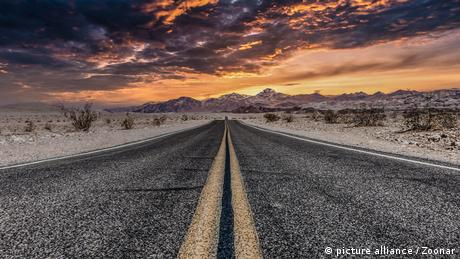 Long stretch of highway with desert on either side and sunset in the horizon