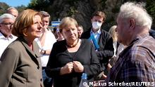 German Chancellor Angela Merkel, center, and Malu Dreyer, left, Prime Minister of Rhineland-Palatinate, talk to residents during their visit to the flood-damaged district Altenburg, part of the municipality of Altenahr, Germany, September 3, 2021. Markus Schreiber/Pool via REUTERS