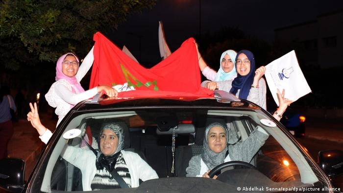 Supporters of the PJD partz in a car with flags.