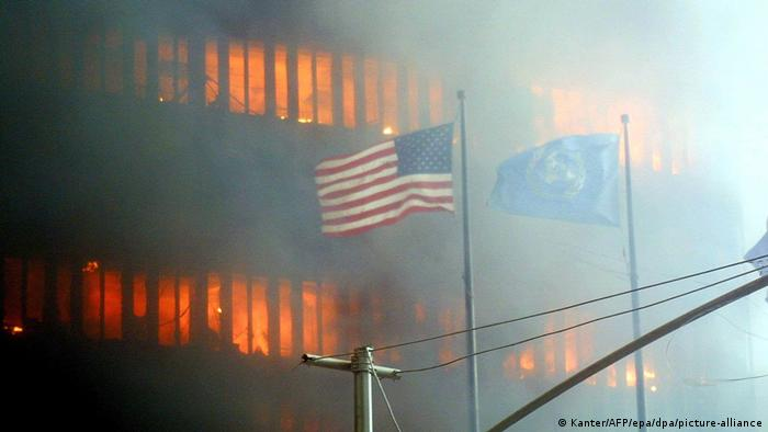 American flag (and UN flag) in front of burning World Trade Center tower