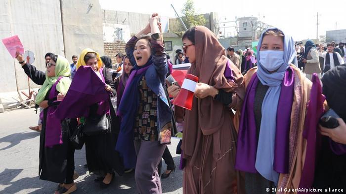 Foto mostra mulheres com véu protestando em uma rua.