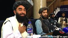 TOPSHOT - Taliban spokesperson, Zabihullah Mujahid (L) attends the first press conference in Kabul on August 17, 2021, following their stunning takeover of Afghanistan. (Photo by Hoshang HASHIMI / AFP) (Photo by HOSHANG HASHIMI/AFP via Getty Images)