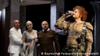 Actors stand and look on during a dress rehearsal at tenor Lance Ryan, costumed as Siegfried