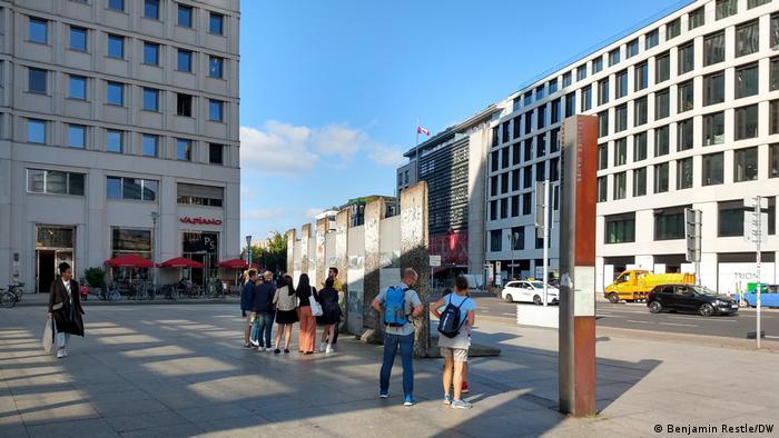 Cole Reulbach und eine Gruppe Touristen stehen vor Überresten der Berliner Mauer am Potsdamer Platz