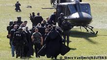 Security personnel escort Patriarch Portfirije and Bishop Joanikije to a helicopter near the monastery in Cetinje, Montenegro, September 5, 2021. REUTERS/Stevo Vasiljevic