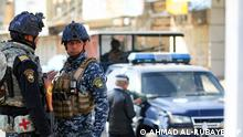 Members of the Iraqi federal police forces stand guard at a checkpoint in a street in the capital Baghdad, during tightened security measure