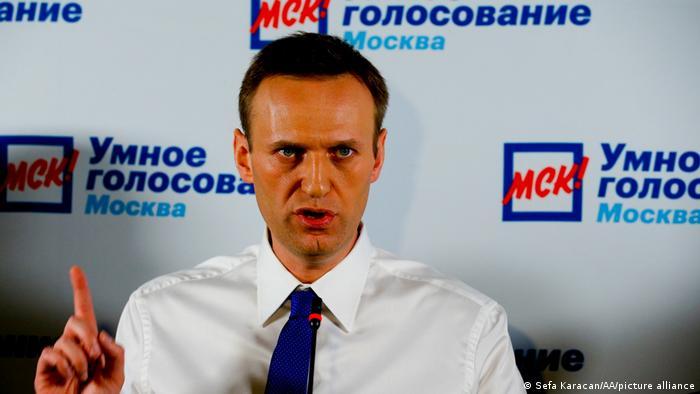 Алексей Навальный на фоне плаката Умное голосование