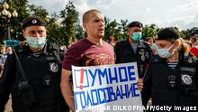 Police officers detain a man with a poster reading Smart voting during an anti-vaccination protest in Moscow on August 14, 2021. - Russia has formally banned organisations established by jailed Kremlin critic Alexei Navalny as the opposition says the authorities are trying to stifle dissent ahead of parliamentary elections. (Photo by Dimitar DILKOFF / AFP) (Photo by DIMITAR DILKOFF/AFP via Getty Images)