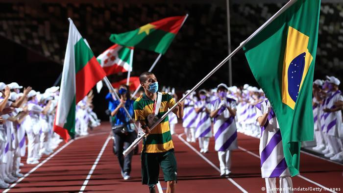 Daniel Dias leva a bandeira do Brasil na pista do estádio. Atrás há outras pessoas com outras bandeiras.