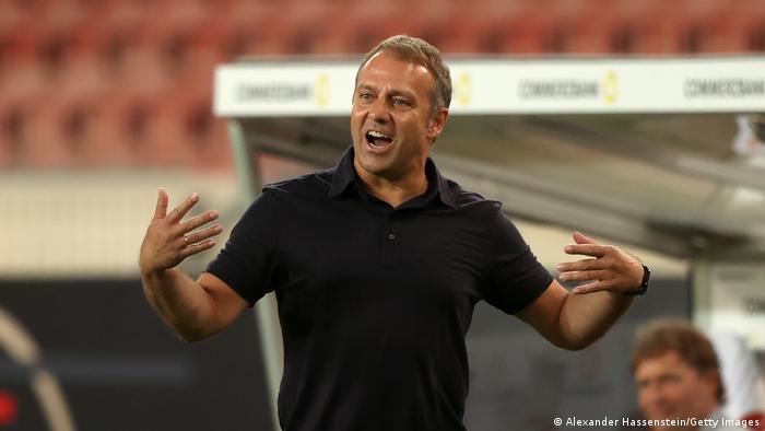 Técnico de futebol Hansi Flick em campo, gesticulando, de braços abertos