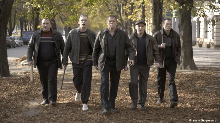 Filmstill Rhino: Fünf Männer mit Schlagstöcken gehen nebeneinander her