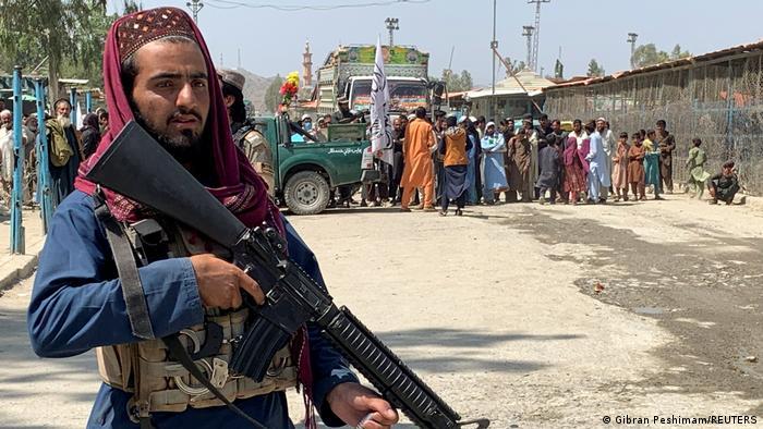 Ein Talibankämpfer mit einer großen Waffe, im Hintergrund eine Menschenmenge an einem Zaun