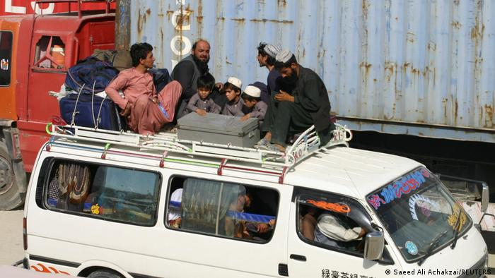 Men and children from Afghanistan sit atop a van with their belongings after crossing into Pakistan