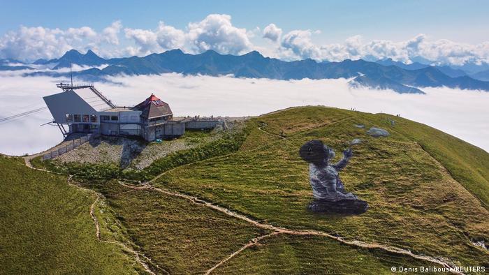 """Francsuki umjetnik Saype, koji je poznat po svojim ogromnim slikama na travi, ovom slikom želi da doprinese dobrom raspoloženju. Na slici je dječak, koji duva balone od sapunice. Za rad su upotrijebljene organski razgradive boje. Grafit, na vrhovima Alpa, """"prostire se"""" na čitavih 1.500 kvadratnih metara."""