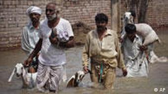 Pakistani villagers make their way through floodwater