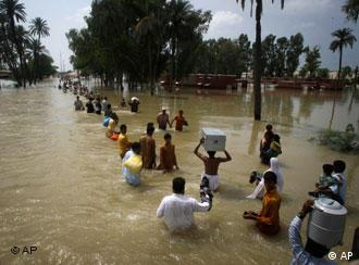 Stranded Pakistani flood victims wade through water