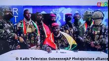 In this image made from video, Col. Mamadi Doumbouya, center, commander of the army's special forces unit, surrounded by others and draped in a Guinean flag, makes an address to the nation from state television headquarters in the capital Conakry, Guinea Sunday, Sept. 5, 2021. Mutinous soldiers in the West African nation detained President Alpha Conde on Sunday after hours of heavy gunfire rang out near the presidential palace in the capital, then announced on state television that the government had been dissolved in an apparent coup d'etat. (Radio Television Guineenne via AP)