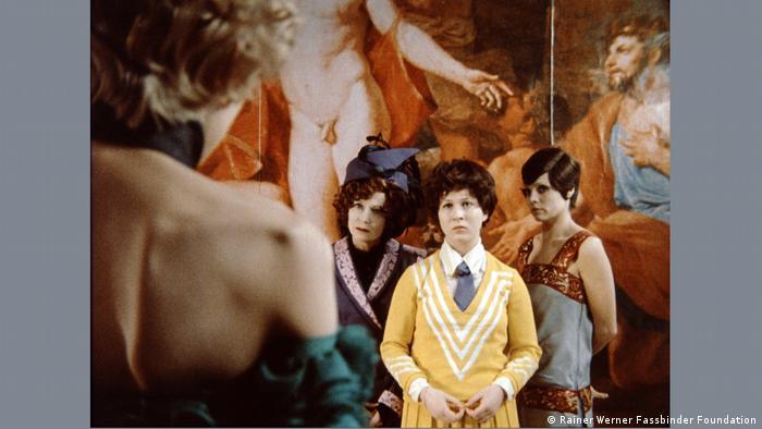 Drei Frauen stehen in einem Museum vor einem barocken Gemälde und schauen eine Frau an