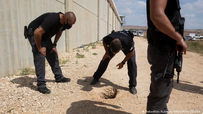 Polizisten schauen sich das Loch im Boden an