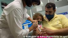 TOPSHOT - Pedro Montano holds his daughter Roxana Montano, 3, while she is being vaccinated against COVID-19 with Cuban vaccine Soberana Plus, on August 24, 2021 at Juan Manuel Marquez hospital in Havana, as part of the vaccine study in children and adolescents. (Photo by ADALBERTO ROQUE / AFP) (Photo by ADALBERTO ROQUE/AFP via Getty Images)