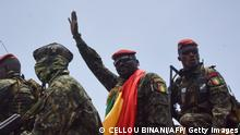 TOPSHOT - Lieutenant Colonel Mamady Doumbouya (C), head of the Armys special forces and coup leader, waves to the crowd as he arrives at the Palace of the People in Conakry on September 6, 2021, ahead of a meeting with the Ministers of the Ex-President of Guinea, Alpha Conde. - Lieutenant Colonel Mamady Doumbouya, the leader of the latest coup in Guinea, is a highly educated, combat-hardened soldier who once served in France's Foreign Legion. Doumbouya's special forces on September 5, 2021 seized Alpha Conde, the West African state's 83-year-old president, a former champion of democracy accused of taking the path of authoritarianism. (Photo by CELLOU BINANI / AFP) (Photo by CELLOU BINANI/AFP via Getty Images)
