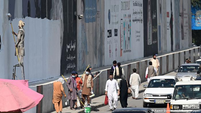 Workers in Kabul paint over murals and pictures of women in Kabul