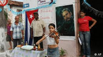 Laura Maria Valdivia plays a song on the violin in celebration of Fidel Castro's 84th birthday at La Caoba neighborhood in Sancti Spiritus, central Cuba, Friday, Aug. 13, 2010. Hanging on the wall are a Cuban flag, left, and a portrait of Fidel Castro, and the sign at center reads in Spanish: Congratulations Commander. (Foto: AP)