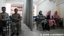 Students attend a class bifurcated by a curtain separating males and females at a private university in Kabul on September 7, 2021, to follow the Taliban's ruling. (Photo by Aamir QURESHI / AFP)