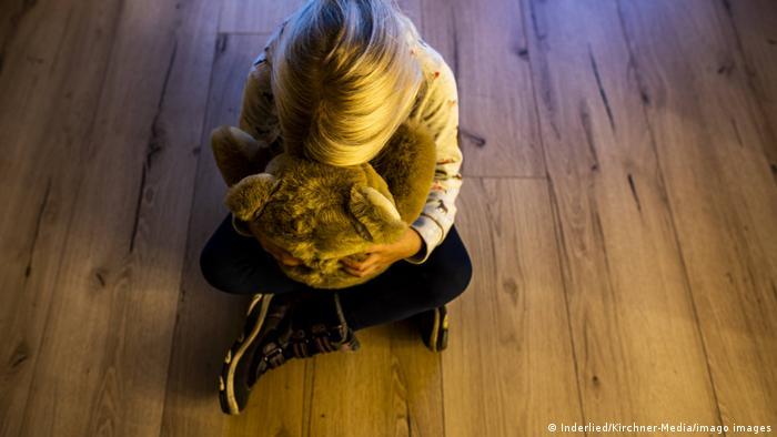 Girl clutching a teddy bear