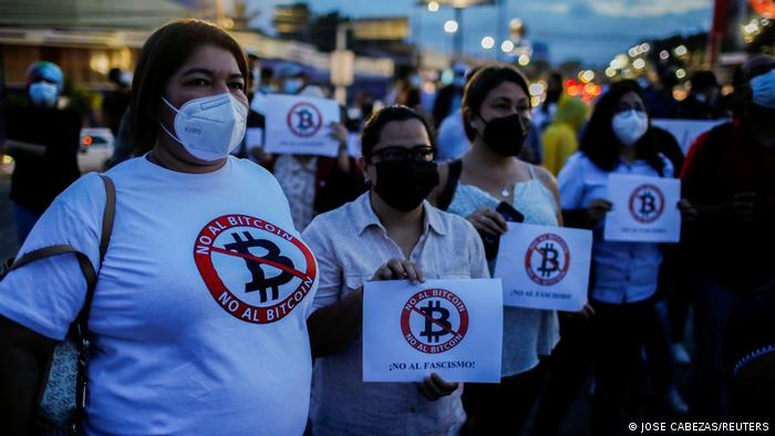 People take part in a protest against the use of Bitcoin as legal tender