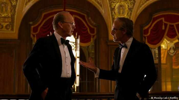 A still from the film featuring Michael Keaton as lawyer Kenneth Feinberg talking to another man.