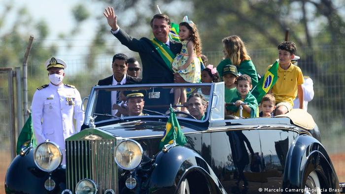 Jair Bolsonaro with children in a car and members of the military