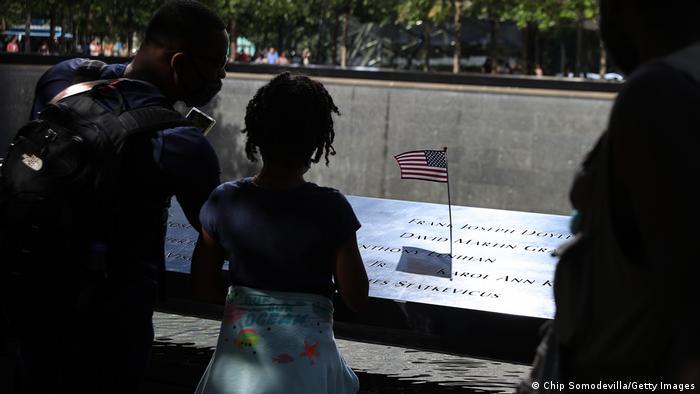 Criança e adulto observam memorial. Eles olham para nomes escritos no monumento. Há uma pequena bandeira dos Estados Unidos sobre um dos nomes.
